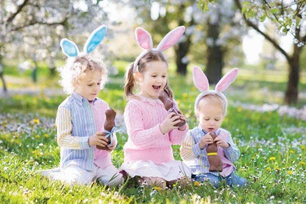 garden easter egg hunt. kids eat bunny chocolate. - buona pasqua in tedesco foto e immagini stock