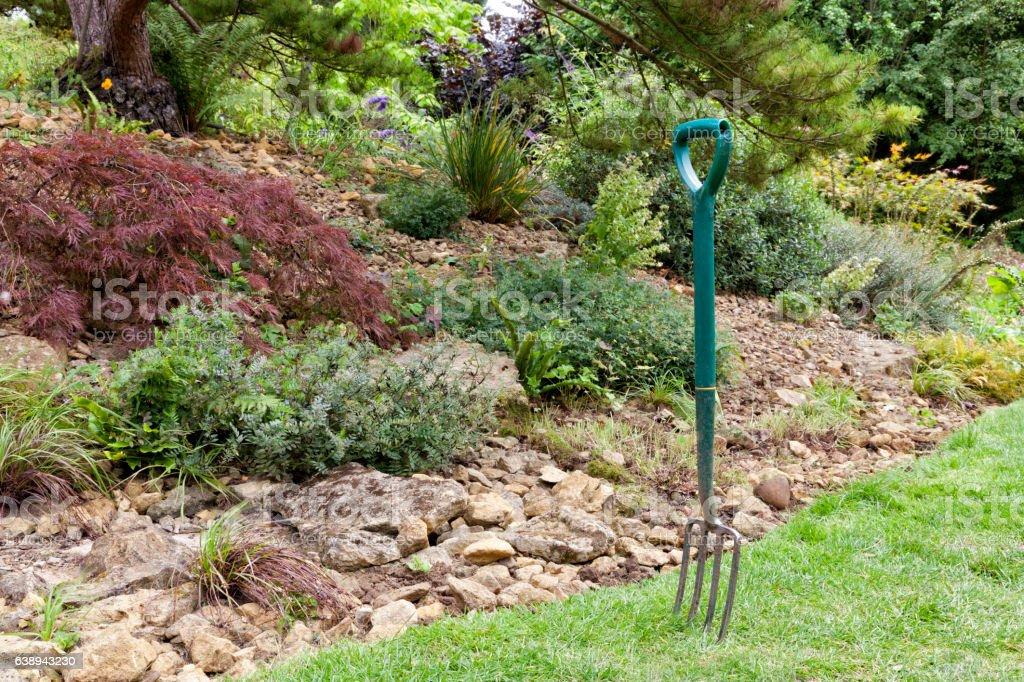 Garden fork by a rockery flowerbed stock photo