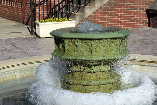 garden fountain in courtyard iced at base - pam schodt stock photos and pictures