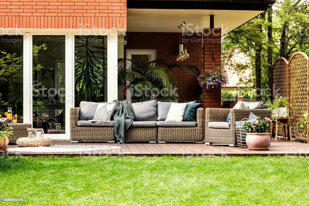 Grey pillows and blanket on garden furniture in front of house in the...