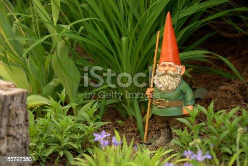 garden gnome with rake and orange pointed cap