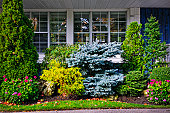 Beautiful garden with trees and flowers in front of windows at home