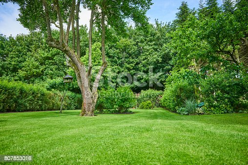 Park-like garden with colorful flowers and nice kept lawn. The house at the end of the garden.