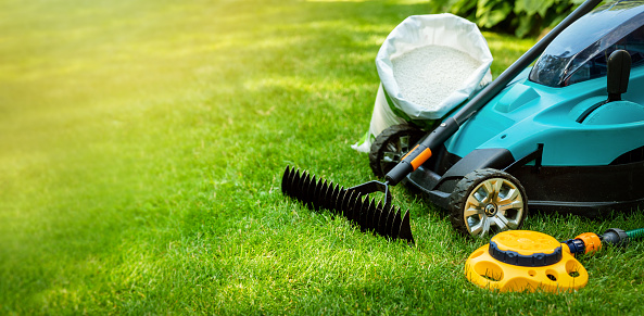 garden lawn care tools and equipment for perfect green grass. banner copy space