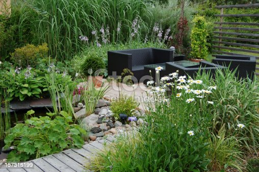 Outdoor garden lounge with a pond and a modern wicker sofa.