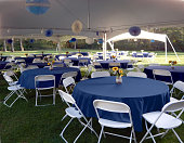 Garden party setup with tables, chairs, tents.  Blue.  White.