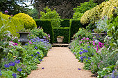 Pathway leading through old fashioned garden borders, shallow depth of field.