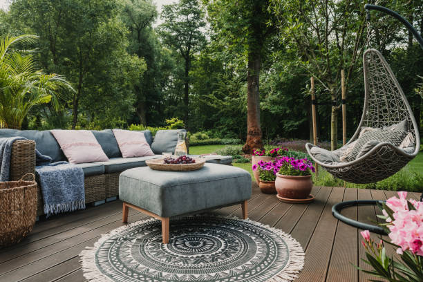 Garden patio decorated with Scandinavian wicker sofa and coffee table Garden patio decorated with Scandinavian wicker sofa and coffee table lawn stock pictures, royalty-free photos & images