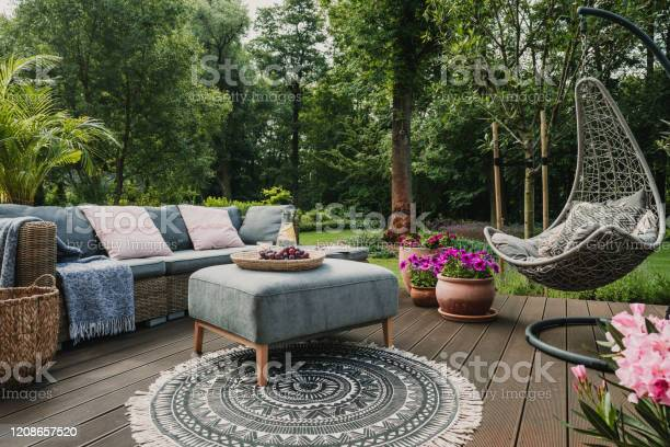 Photo of Garden patio decorated with Scandinavian wicker sofa and coffee table
