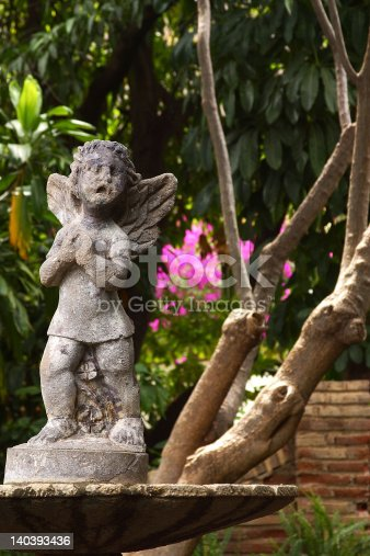 sculpture of an angel in a fountain of a garden
