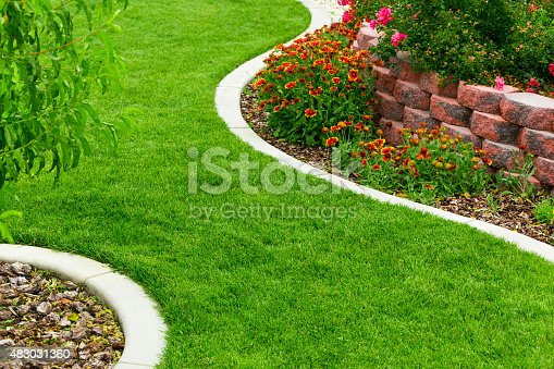 Garden with green lawn and colorful flowers.