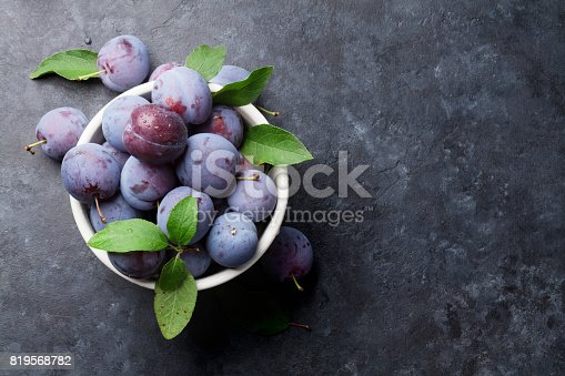 istock Garden plums in bowl on stone table 819568782