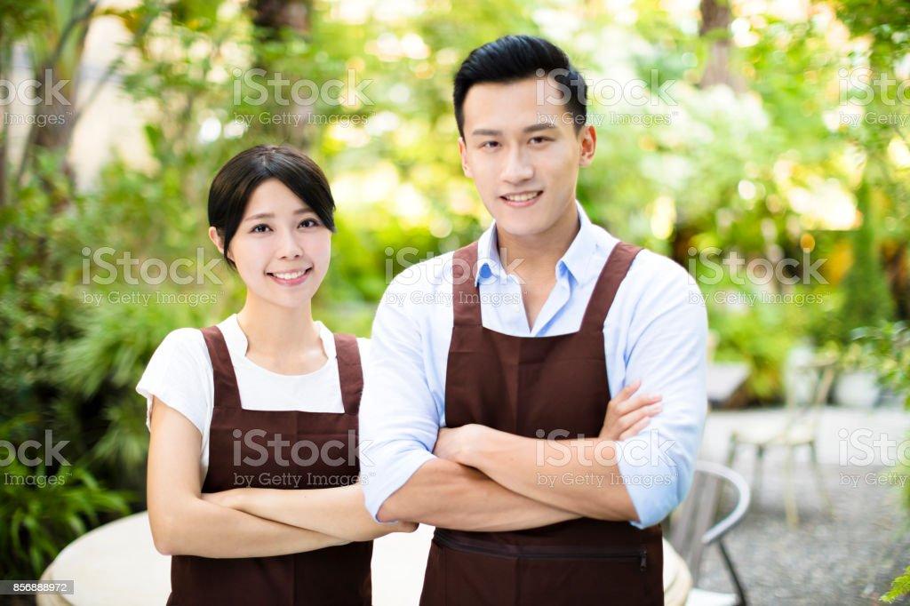 garden restaurant owner standing with partner stock photo