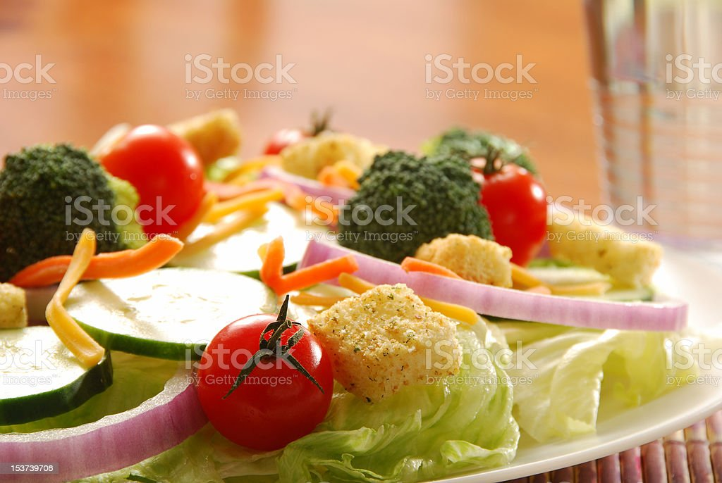 Garden salad on table setting with glass of water stock photo