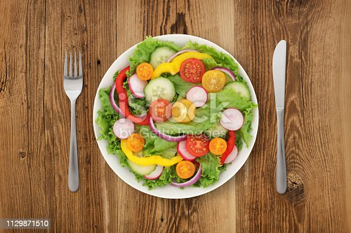 Colorful garden salad with knife and fork on wooden background