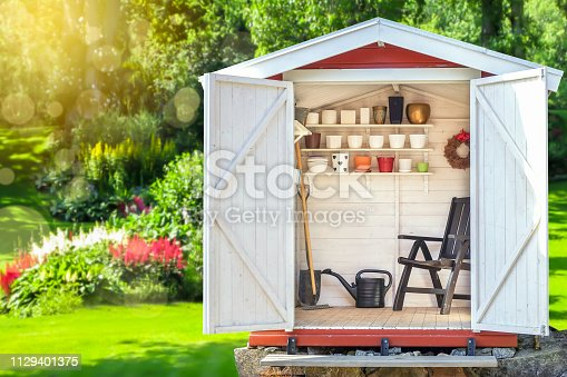 istock Garden shed filled with gardening tools with green sunny garden in the background. 1129401375