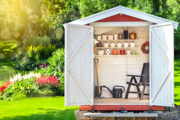 Garden shed filled with gardening tools with green sunny garden in the background. Garden shed filled with gardening tools. Shovels, rake, pots, water pitcher in storage hut. Green sunny garden in the background. shed stock pictures, royalty-free photos & images