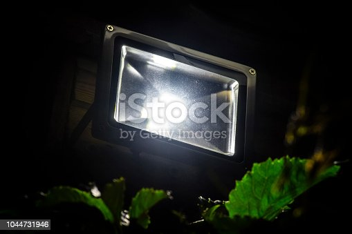 Garden LED spotlight on a wooden building close-up.