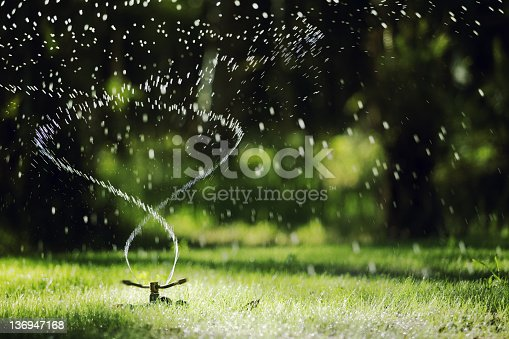 Narrow depth of field Sprinkler head sprinkles water on grass with bokeh backgound
