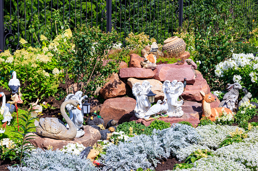 Garden statues of angels and animals on flowerbed