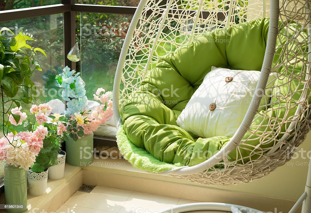 garden swing with mattress and cushion in a balcony stock photo