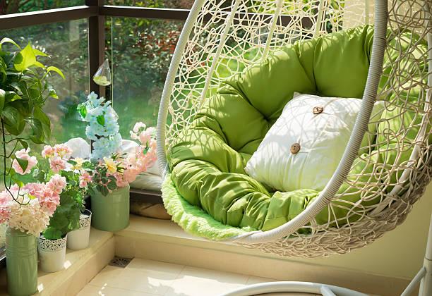 garden swing with mattress and cushion in a balcony - schommelen bungelen stockfoto's en -beelden