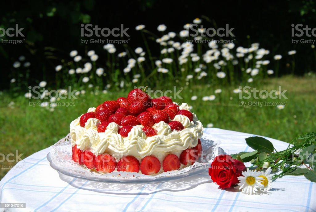 Garden table with a strawberry cake and summer flowers stock photo