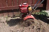 Garden tiller turning over soil