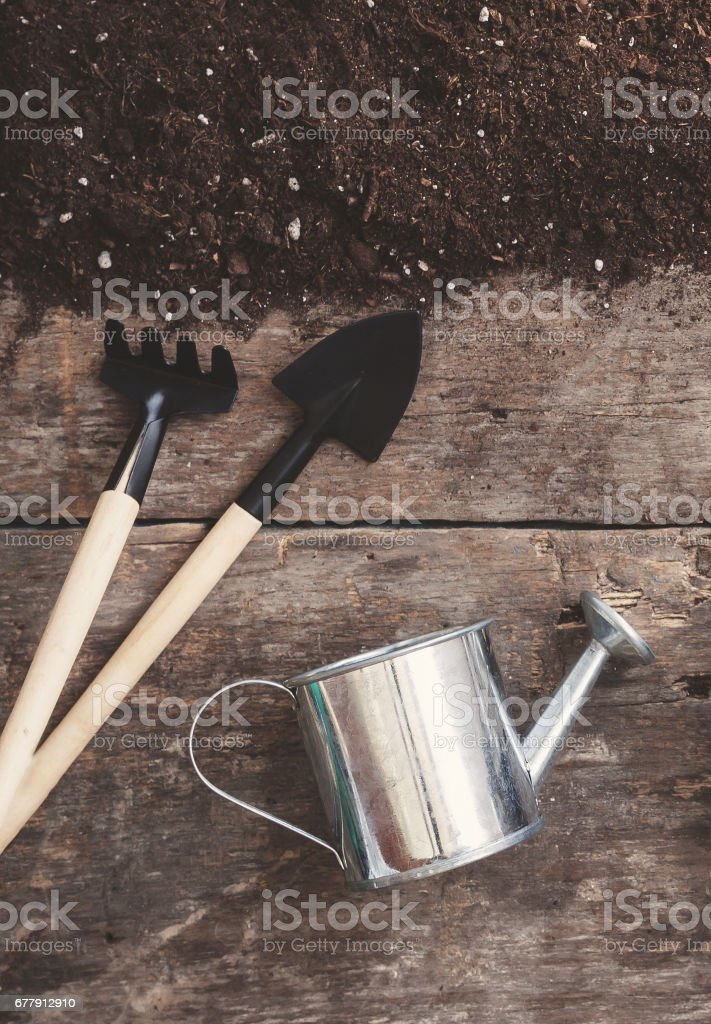 A garden tool, a shovel, a rake, a watering can, a bucket, tablets for plants, earth-soil scattered on a wooden old brown background, close-up. Concept of gardening royalty-free stock photo