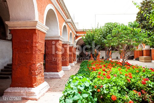 Garden with flowers and trees in monastery Saint Catalina, Arequipa, Peru. Columns in the building