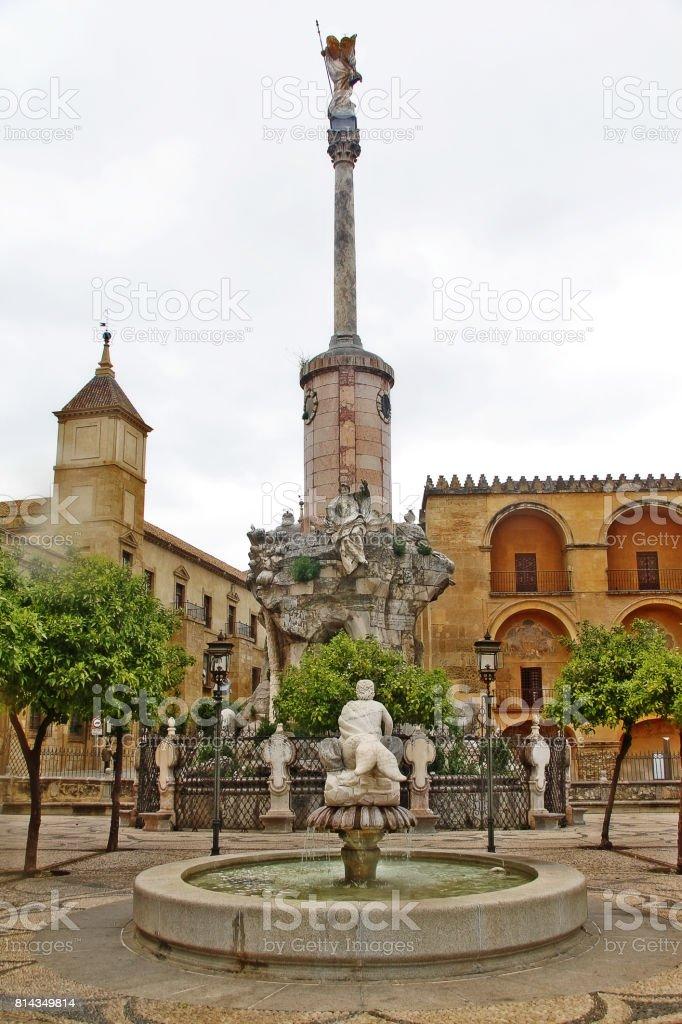 Jardín con fuente y San Rafaels puerta puente monumento triunfo (Triunfo de San Rafael) en la Puerta del Puente en la Plaza del Triunfo (Plaza del triunfo de San Rafael), Córdoba, Andalucía, España - foto de stock