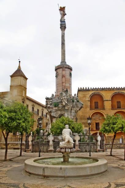 Jardim com fonte e San Rafaels Portão ponte triunfo monumento (Triunfo de San Rafael) em Puerta del Puente na Plaza del Triunfo (Praça do triunfo de San Rafael), Córdoba, Andaluzia, Espanha - foto de acervo