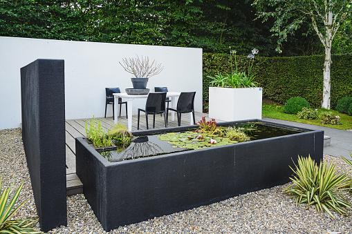 Garden with modern garden furniture and trendy pond.