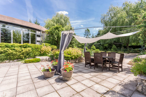 Garden with paved terrace with table View of a garden with the paved terrace area with dining table, garden chairs and plants around in a sunny day war effort stock pictures, royalty-free photos & images