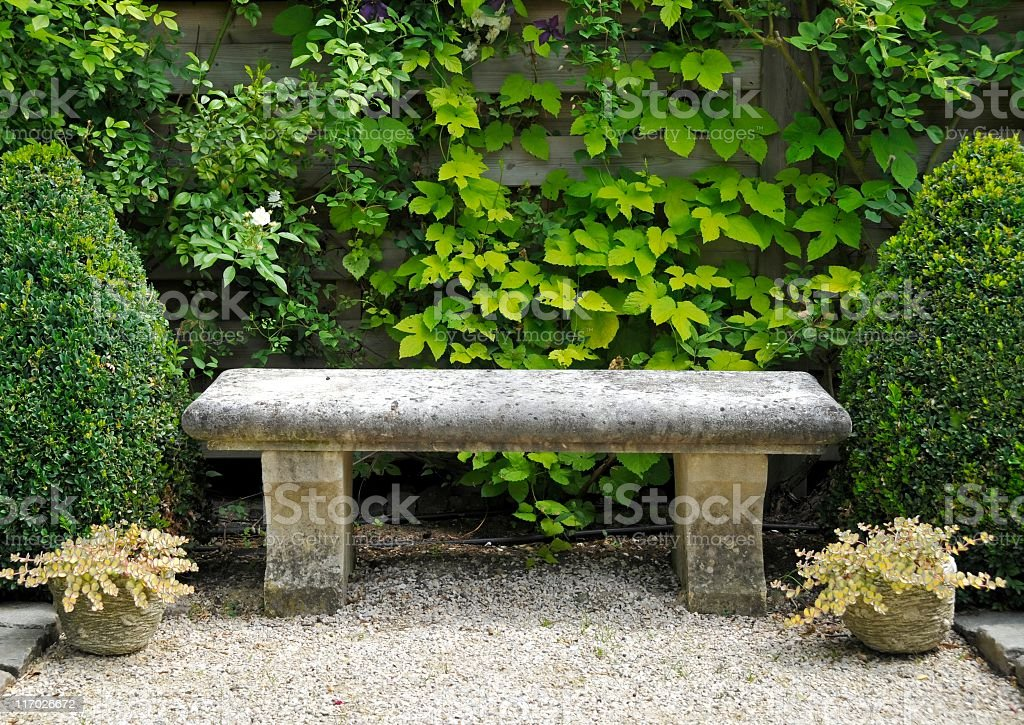 Garden with stone bench , buxus plants and potted sedum plants. stock photo