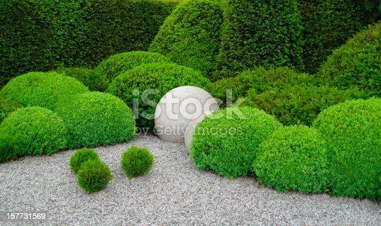 Gardendesign with buxus balls, yew  and stone balls