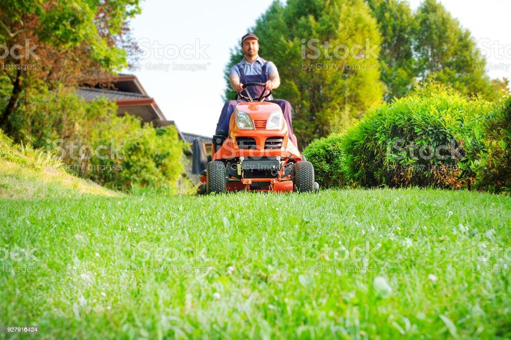Gardener driving a riding lawn mower in garden stock photo
