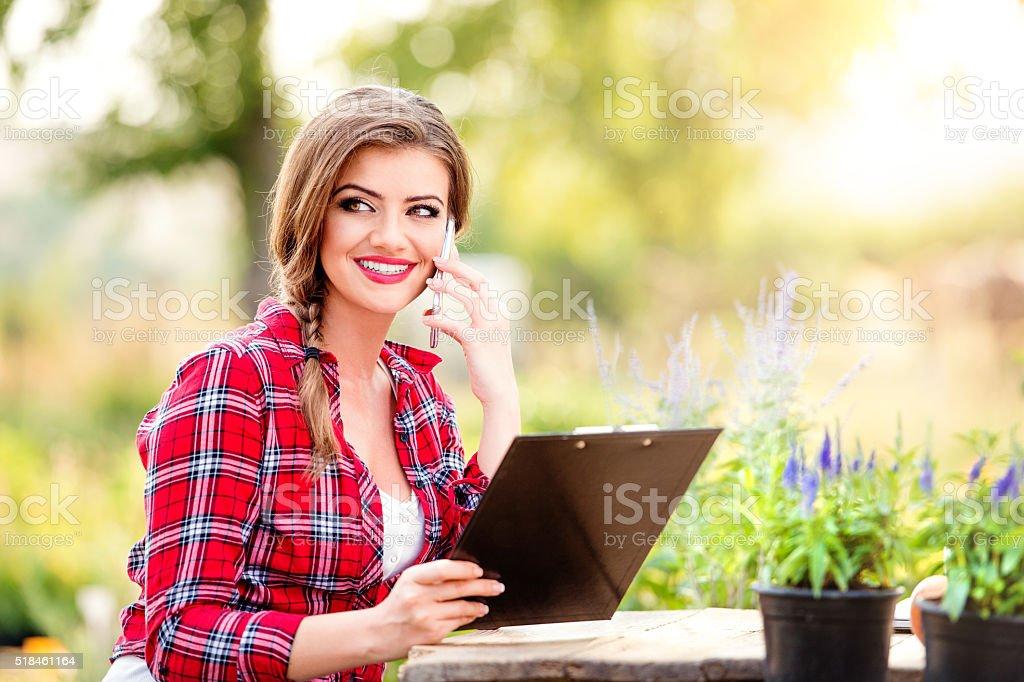 Gardener holding clipboard, making phone call, green sunny natur royalty-free stock photo