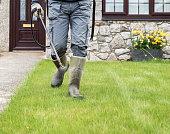 Gardener horticulturalist spraying weed killer on lawn - garden maintenance