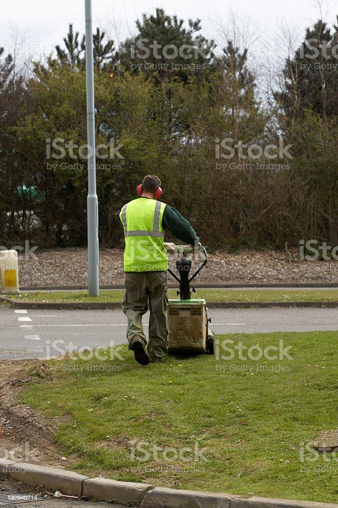 Gardener mowing grass verge e stock photo