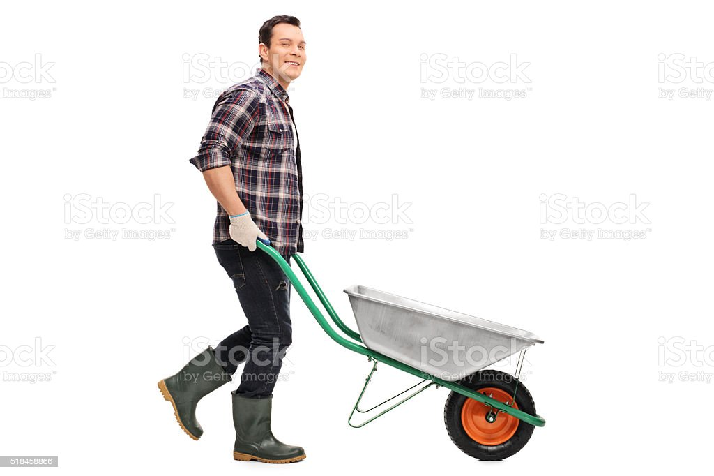 Gardener pushing an empty wheelbarrow stock photo