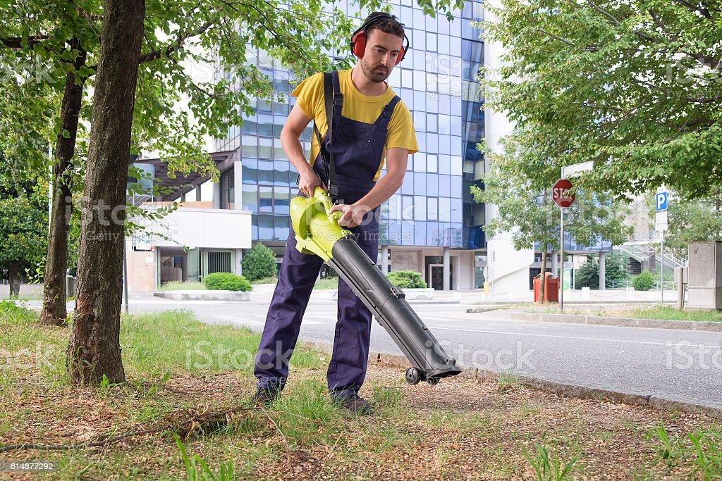 Gardener using his leaves blower in the garden stock photo
