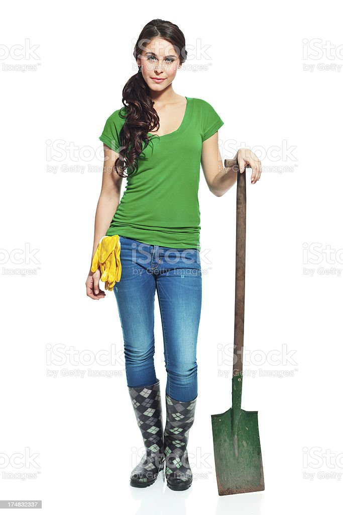 Gardener with spade Full lenght portrait of beautiful gardener standing with a spade and smiling at the camera. 20-24 Years Stock Photo
