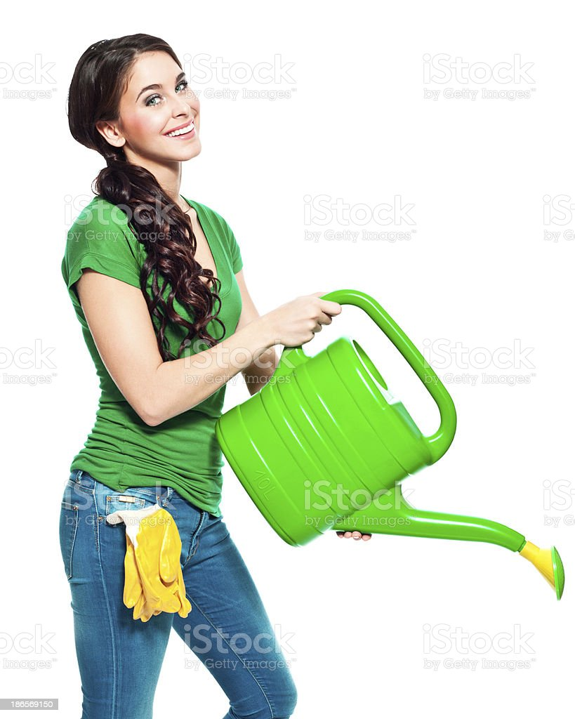 Gardener with watering can Portrait of beautiful gardener holding a watering can in her hands and smiling at the camera. 20-24 Years Stock Photo