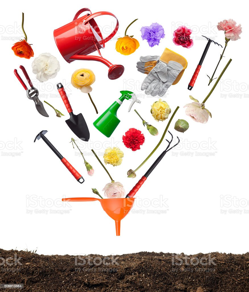 Gardening Equipments And Flowers Falling Into Funnel On White Background stock photo