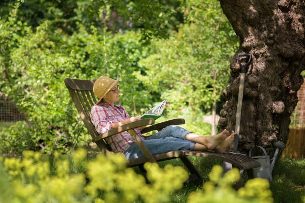 Gardening - senior woman in deck chair enjoy relaxing in garden outdoors stock photo
