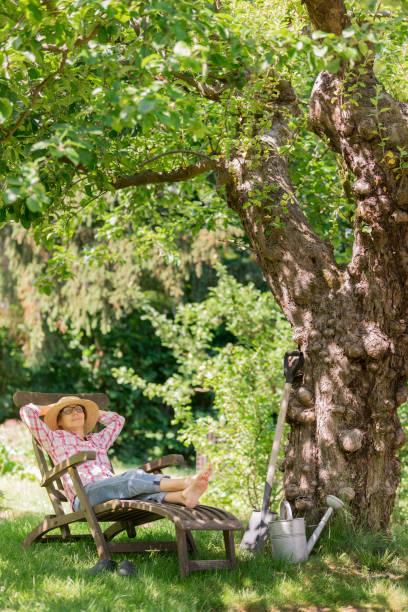 Gartenarbeit - Seniorin im Liegestuhl entspannen im Garten im Freien – Foto