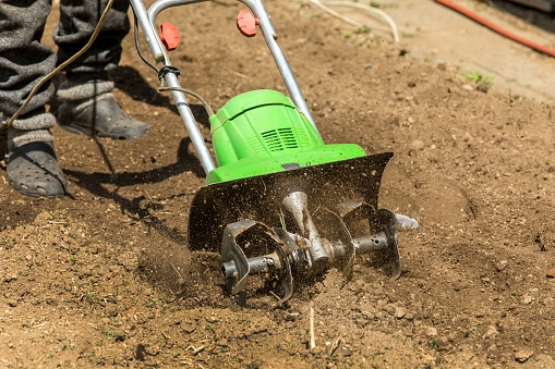 Gardening. Spring work on the farm. Land cultivation with an electric cultivator. Man plows the earth with an electric cultivator.
