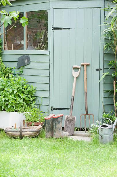 gärtnern tools vor der tür von schuppen - schuppen türen stock-fotos und bilder