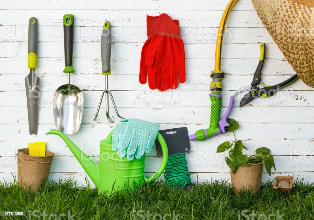 Gardening tools and a straw hat on the grass in the garden. royalty-free stock photo